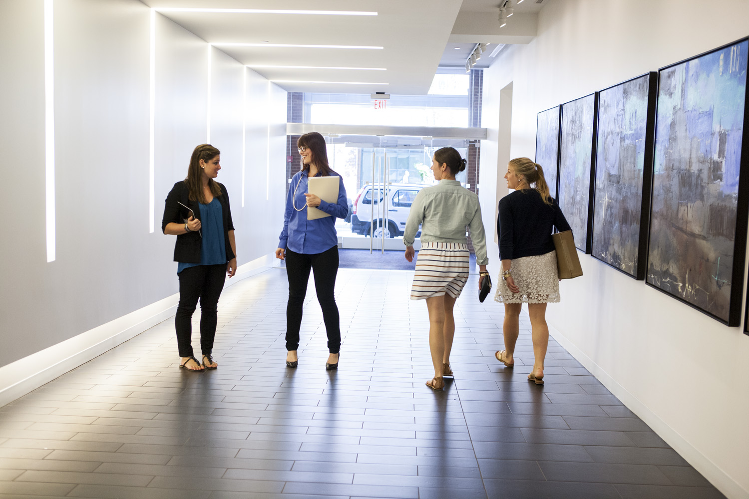 Four young women talking in a hallway
