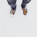 The two feet of a Young adult wearing laced boots in about 3 inches of snow.