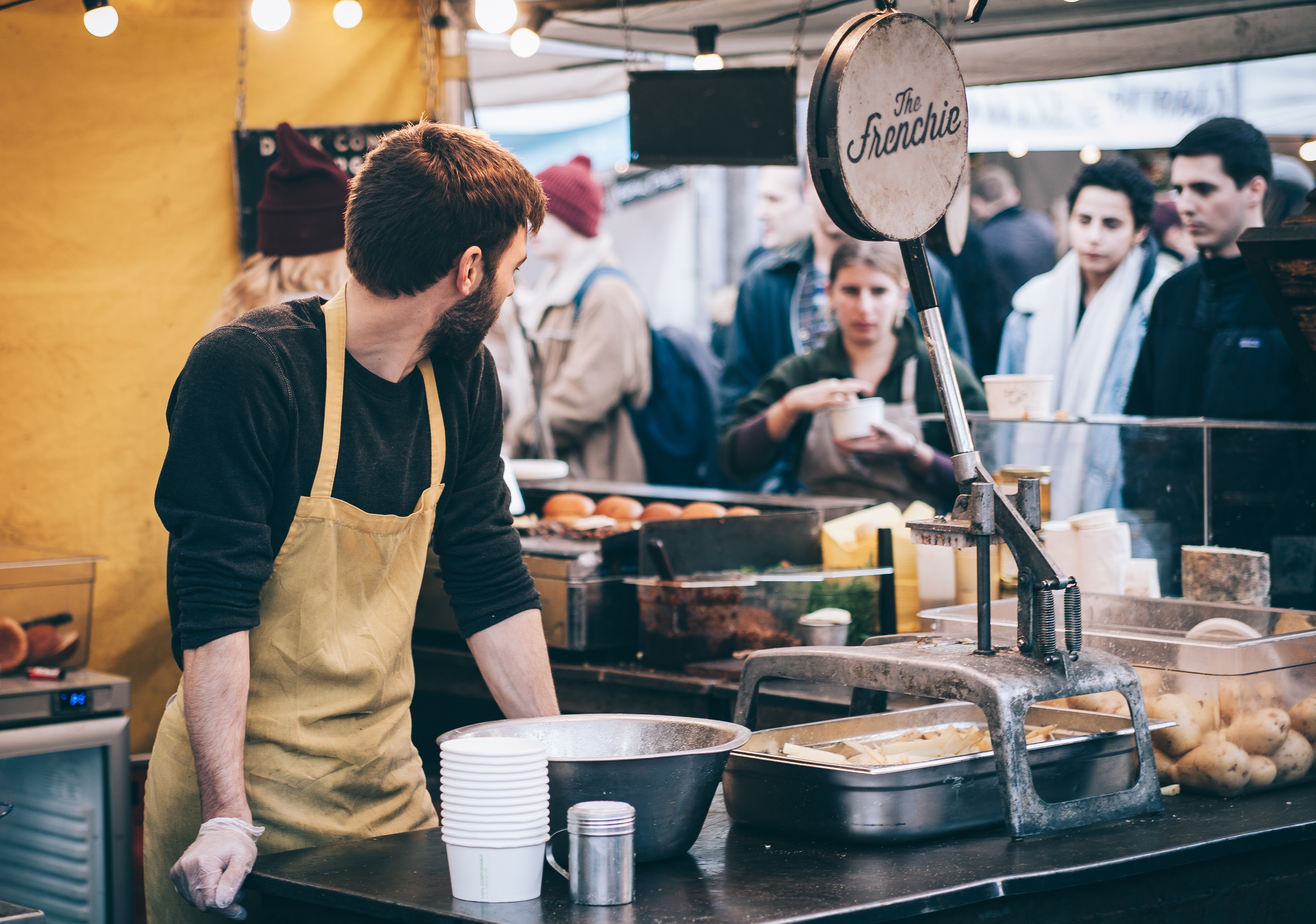employee wearing an apron looks over his shoulder at a line of customers