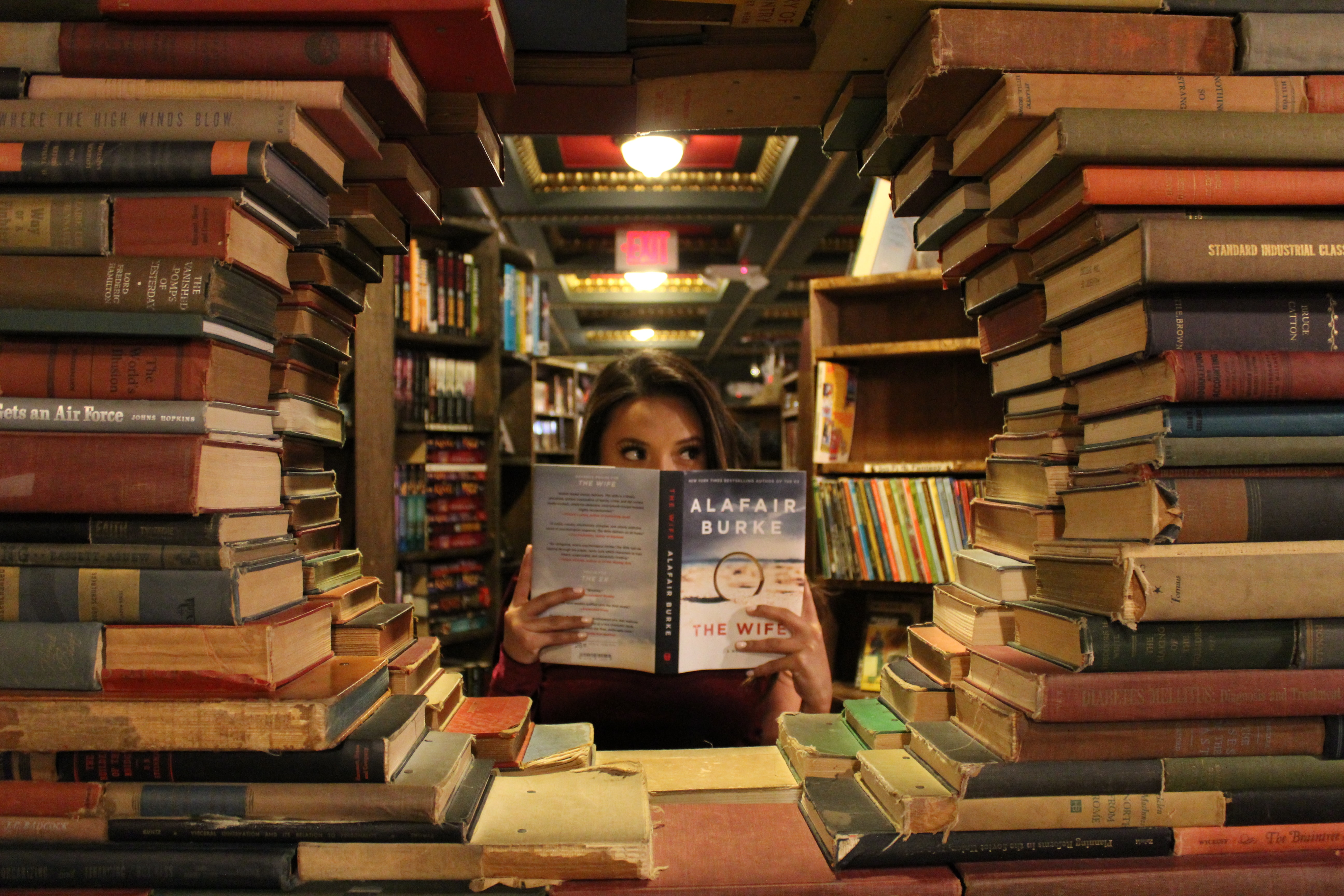 Stacks of books with a circular opening. A woman holds a book.